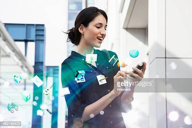 Young businesswoman holding smartphone with apps and icons coming out of it