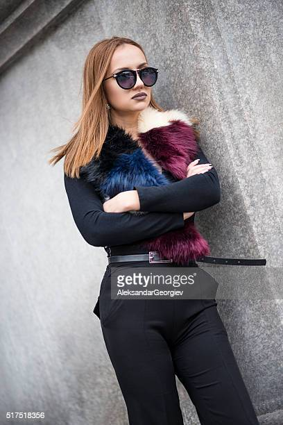 Young Businesswoman how Leaning on Office Building Wall