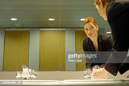 Young businesswoman in bathroom, washing hands