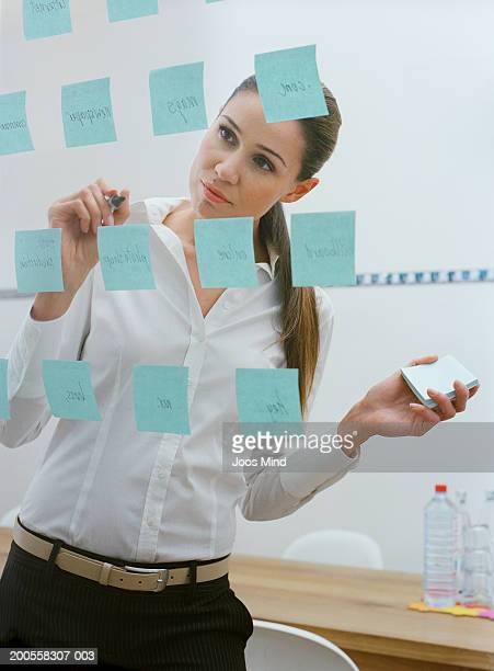 Young businesswoman in office, sticking memo notes on glass wall
