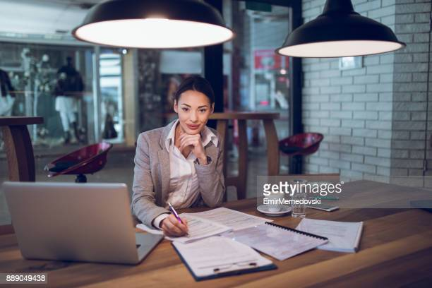 Young businesswoman in the office brainstorming over business report.