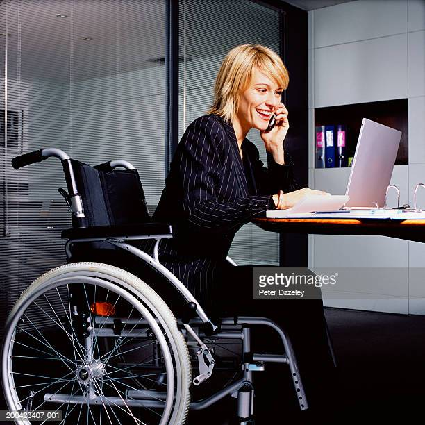 Young businesswoman in wheelchair working on laptop using mobile