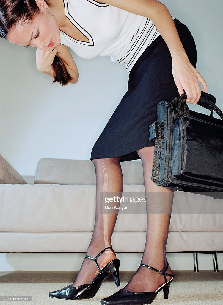 Young businesswoman inspecting ladder in tights, low angle view : Stock Photo