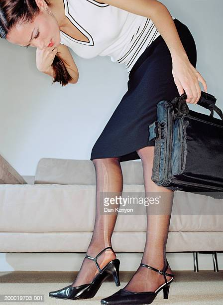 Young businesswoman inspecting ladder in tights, low angle view