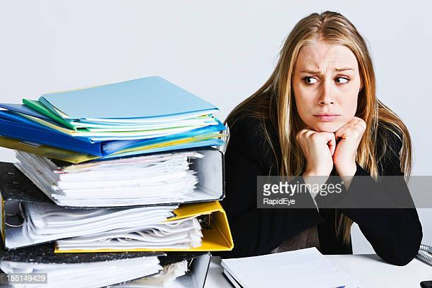 Young businesswoman is seriously bothered by work overload