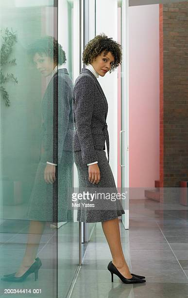 Young businesswoman leaning against office window, portrait