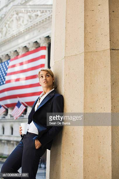 Young businesswoman leaning on building wall with American flag in background