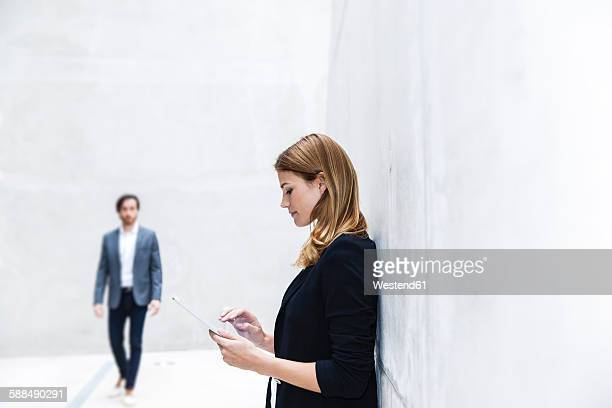 Young businesswoman leaning on concrete wall using digital tablet
