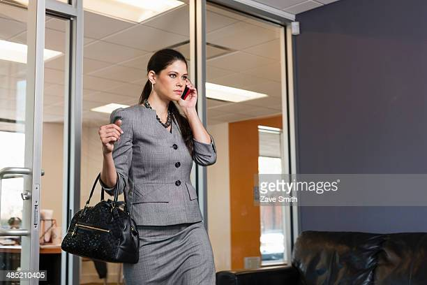Young businesswoman leaving office, on phonecall
