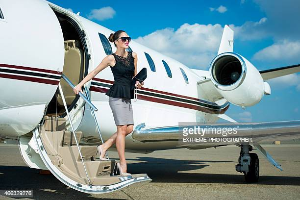 Young businesswoman leaving private jet airplane