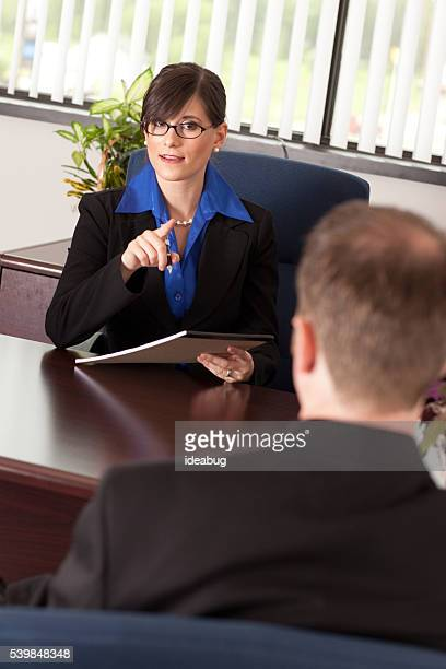 Young Businesswoman Lecturing a Businessman at Desk in Office