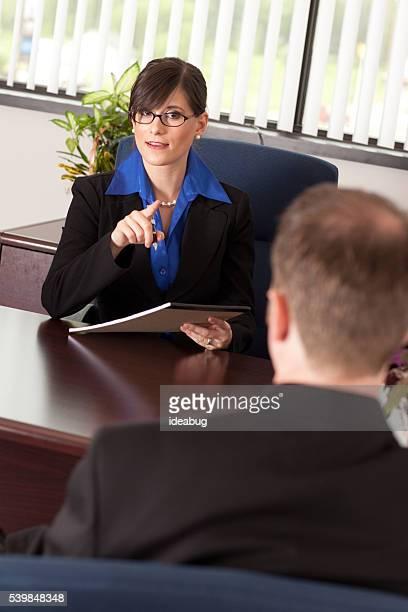 Mulher de Negócios jovem Palestras um homem de negócios na mesa no escritório