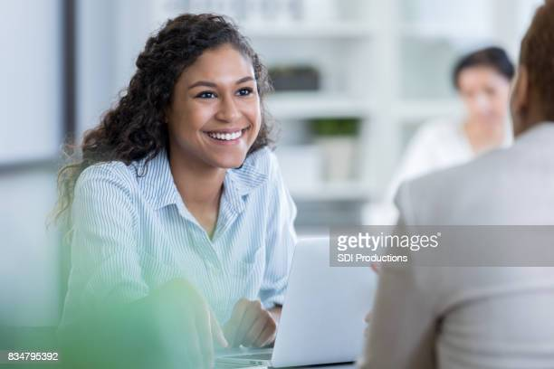 Young businesswoman listens attentively to coworker