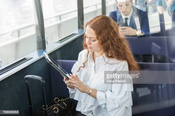 Young businesswoman looking at digital tablet on passenger ferry