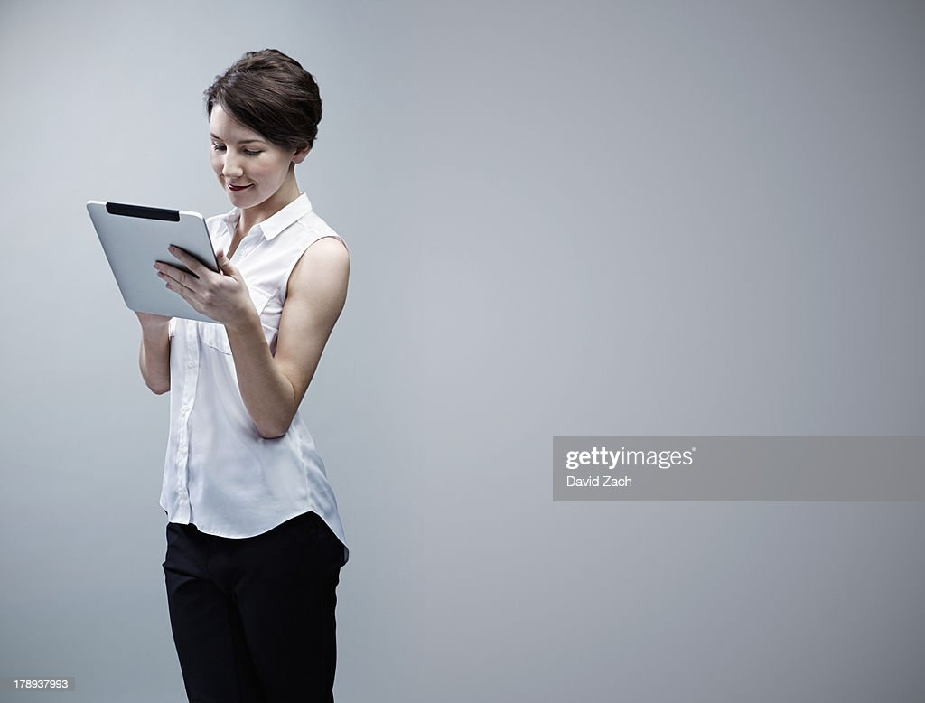 Young businesswoman looking at digital tablet : Stock Photo