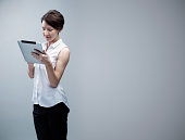 Young businesswoman looking at digital tablet
