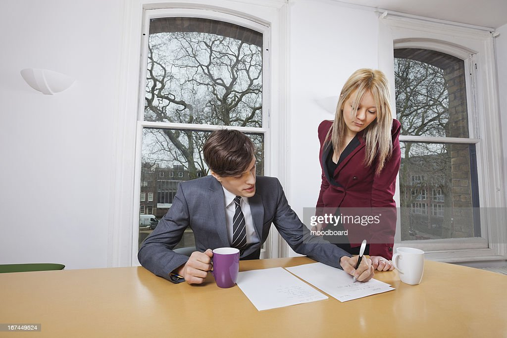 Young businesswoman looking at male colleague signing documents at conference table : Stock Photo