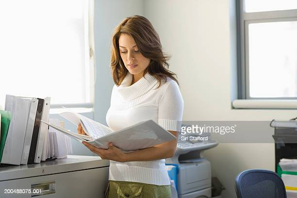 Young businesswoman looking at paperwork in binder