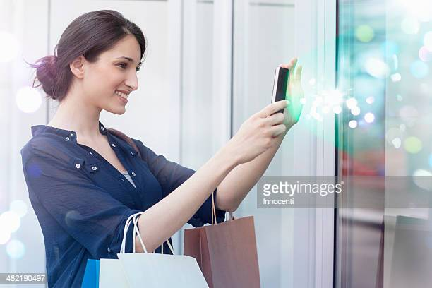 Young businesswoman looking at smartphone with lights coming out of it