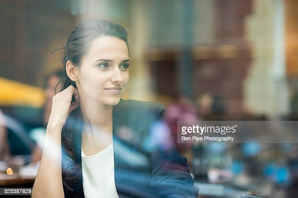 Young businesswoman looking out of cafe window, London, UK