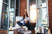 Young businesswoman meditating sitting on working table in lotus pose in her office.