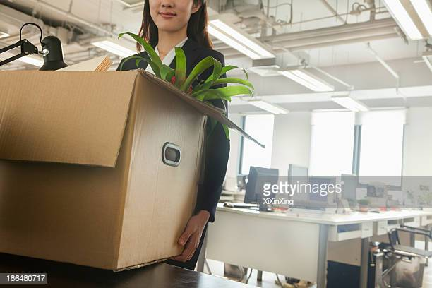 Young businesswoman moving box with office supplies