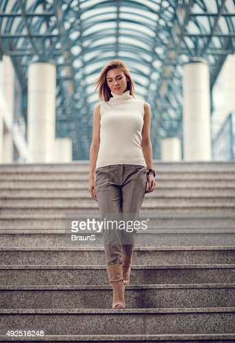 Young businesswoman moving down the stairs.