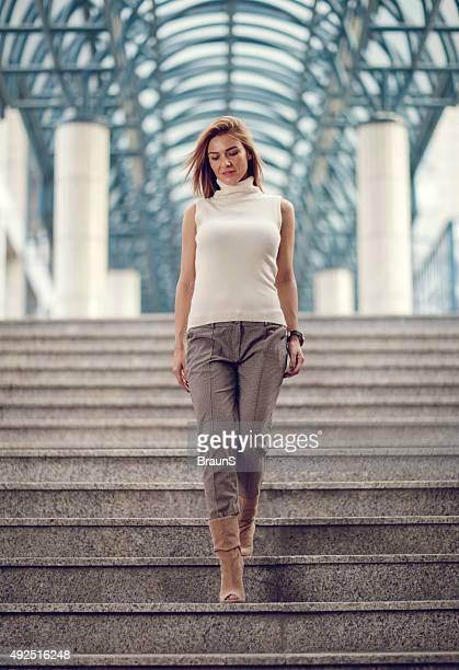 Jeune femme d'affaires en mouvement sur les escaliers.