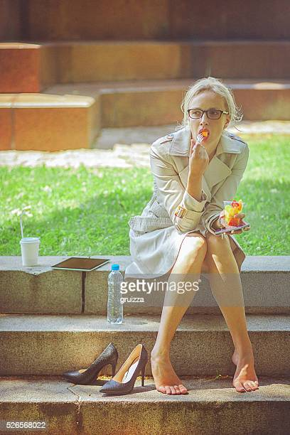 Young businesswoman on a lunch break in park
