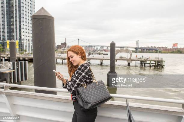 Young businesswoman on ferry deck looking at smartphone, New York, USA