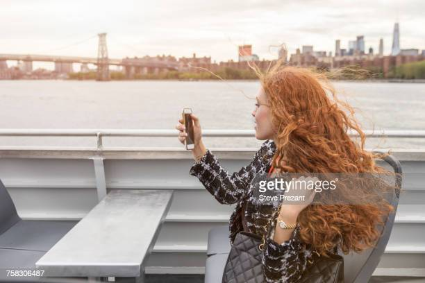 Young businesswoman on passenger ferry deck taking smartphone selfie