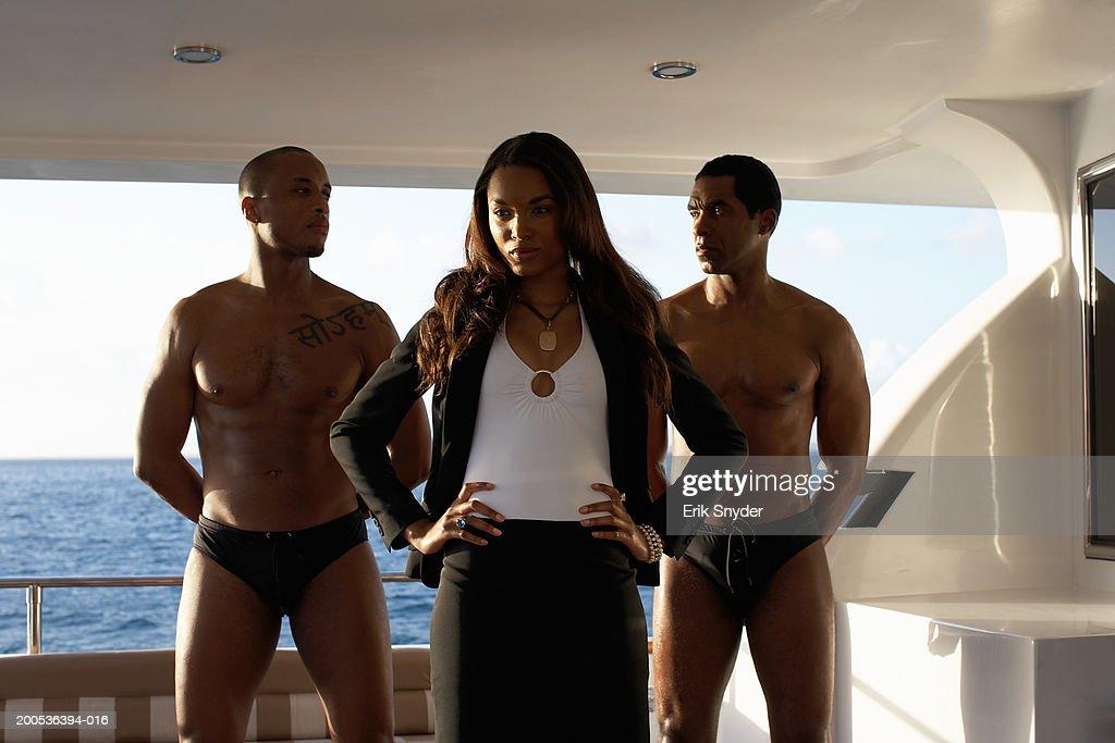 Young businesswoman on yacht between men wearing swim trunks : Stock Photo