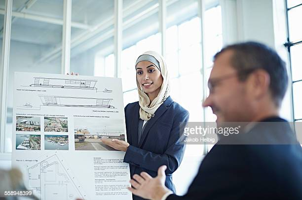 Young businesswoman presenting ideas to businessman in office
