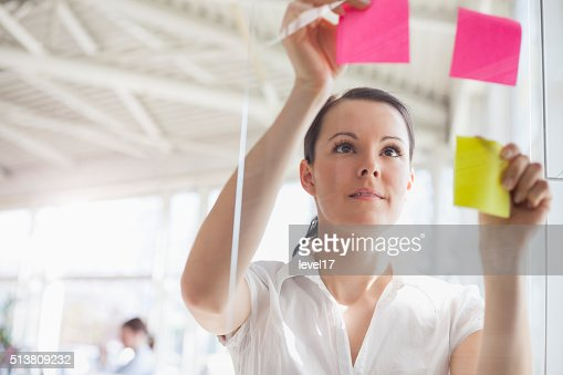 Young businesswoman putting adhesive notes on glass wall in office : Stock Photo