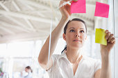 Beautiful young businesswoman putting adhesive notes on glass wall in office
