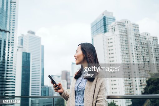 Young businesswoman reading emails on smartphone by the terrace of office building : Stock Photo
