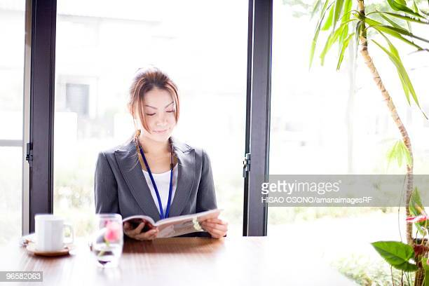 Young businesswoman reading magazine in cafe