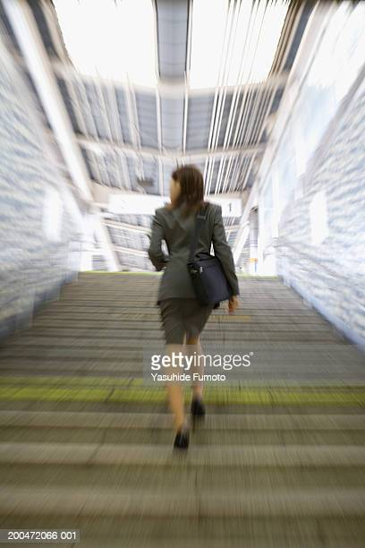 Young businesswoman running up stairway, rear view (blurred motion)