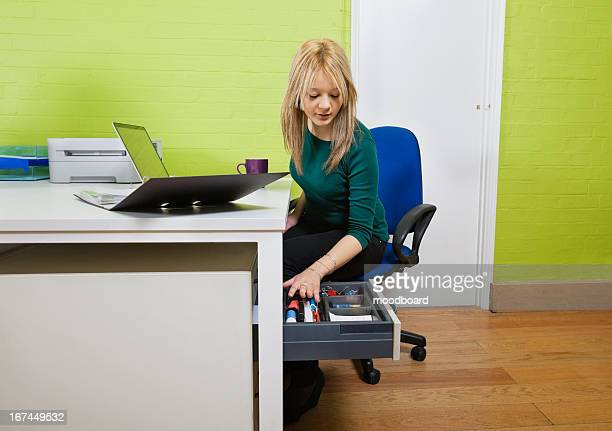 Young businesswoman searching something in drawer with laptop and file folder on desk