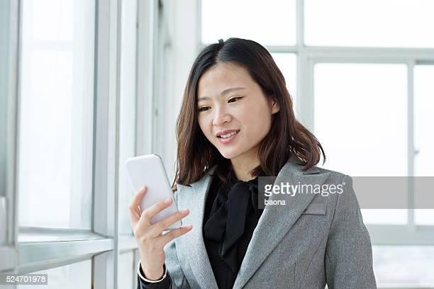 Young businesswoman sending a text