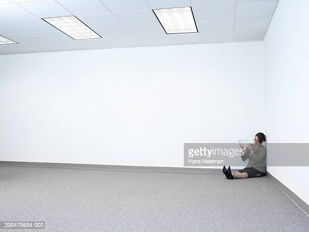 Young businesswoman sitting against wall in empty office space