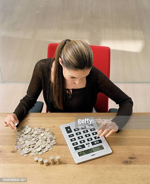 Young businesswoman sitting at desk, counting money using calculator
