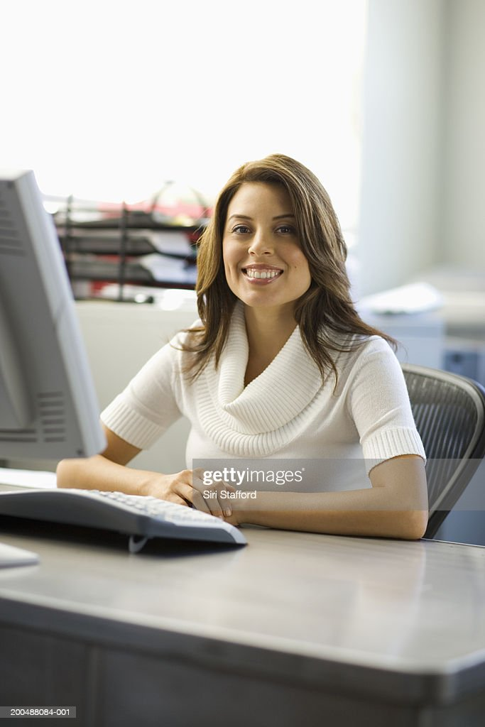 Young businesswoman sitting at desk : Stock Photo