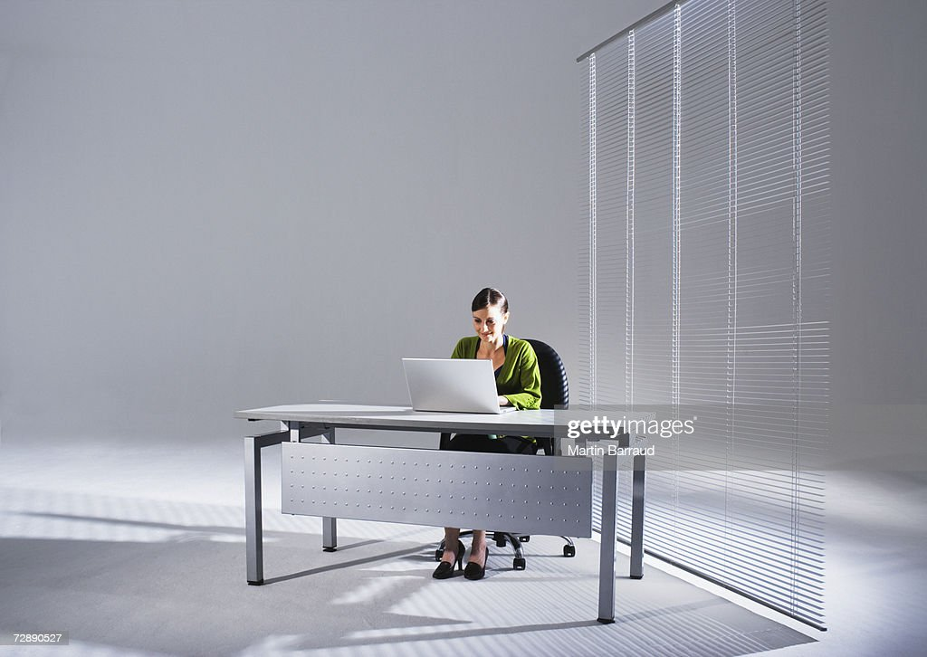 Young businesswoman sitting at desk, using laptop