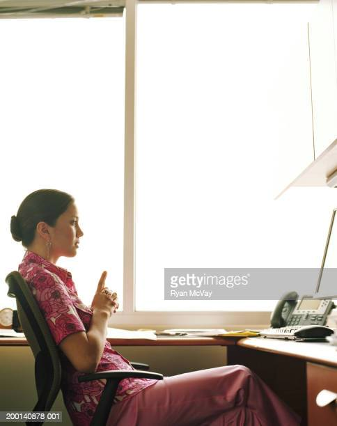 Young businesswoman sitting at office desk, side view