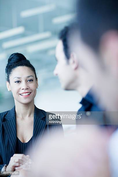 Young businesswoman sitting in a business meeting with colleagues
