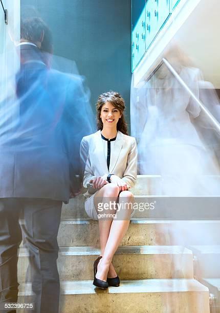Jeune femme d'affaires assis sur l'escalier