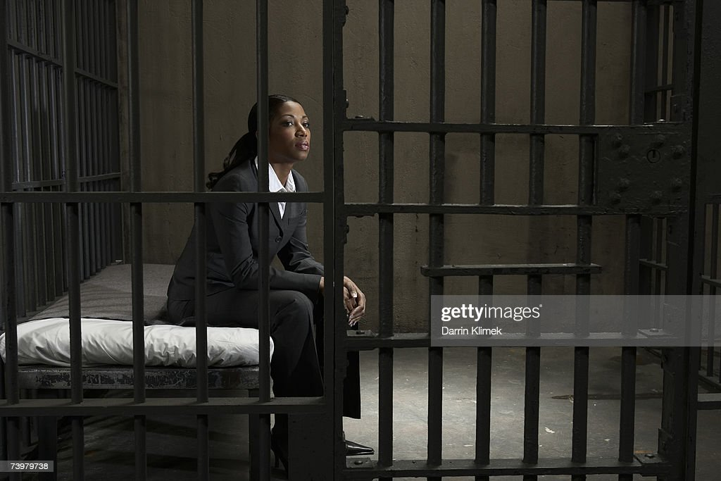 Young businesswoman sitting on bed in prison cell, looking away : Stock Photo