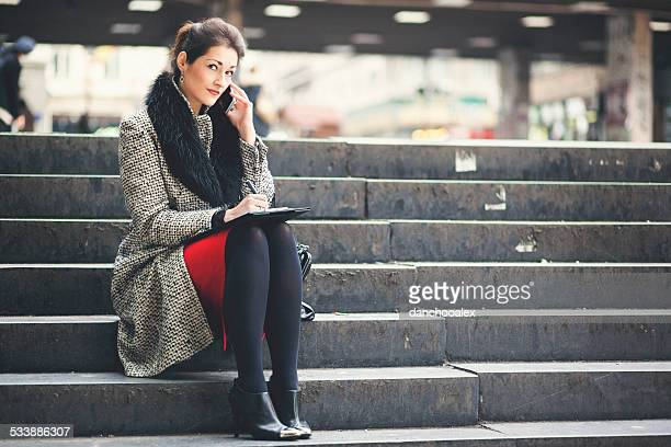 Young businesswoman sitting on stairs a using cell phone
