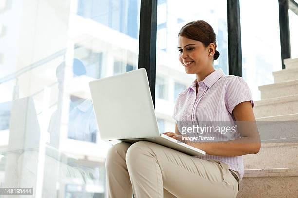Jeune femme d'affaires assis sur les escaliers et à l'aide d'un ordinateur portable